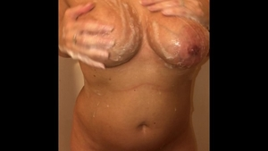 Busty female masturbating in shower solo